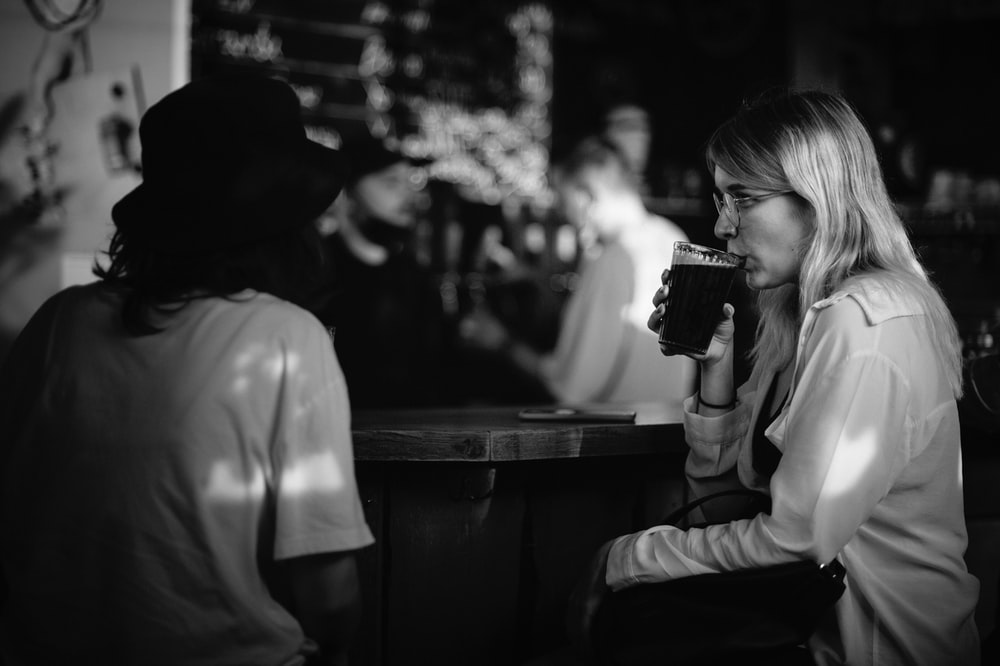 grayscale photo of woman drinking from cup