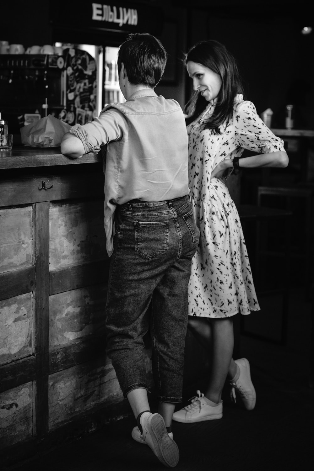 grayscale photo of man and woman standing beside wooden table
