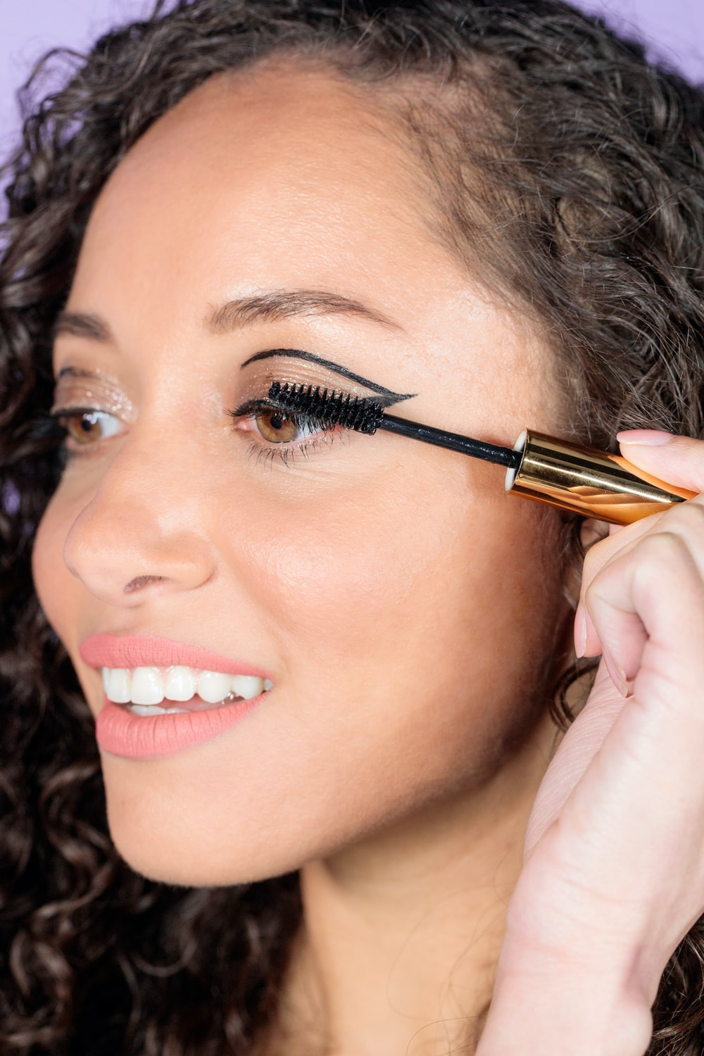 woman with black hair holding brown and black makeup brush