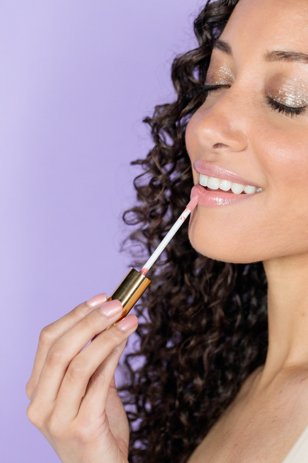 woman holding black and gold lipstick