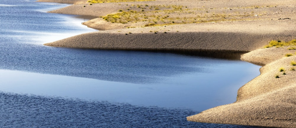 blue body of water near brown sand during daytime
