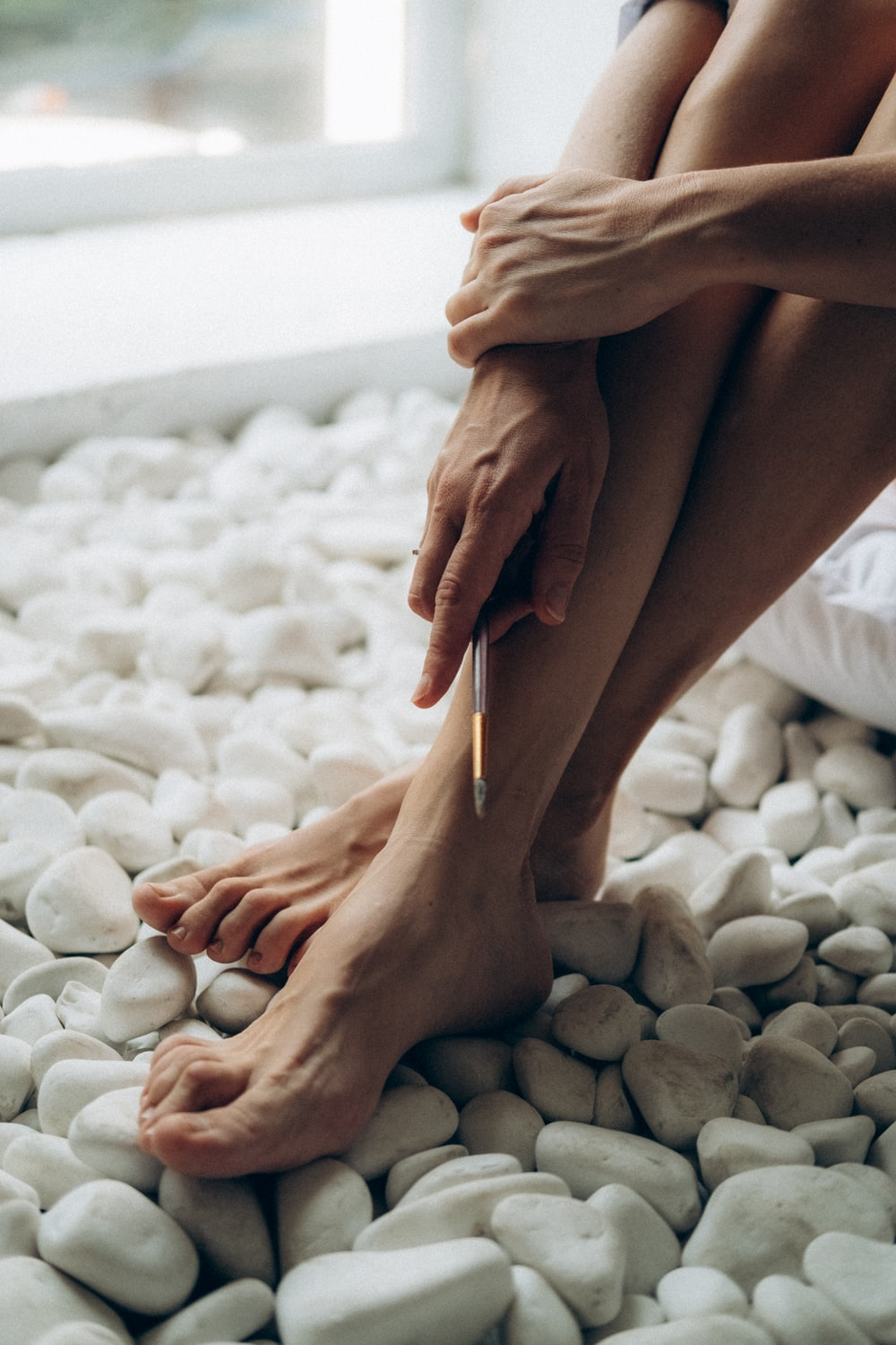 persons feet on white and gray pebbles