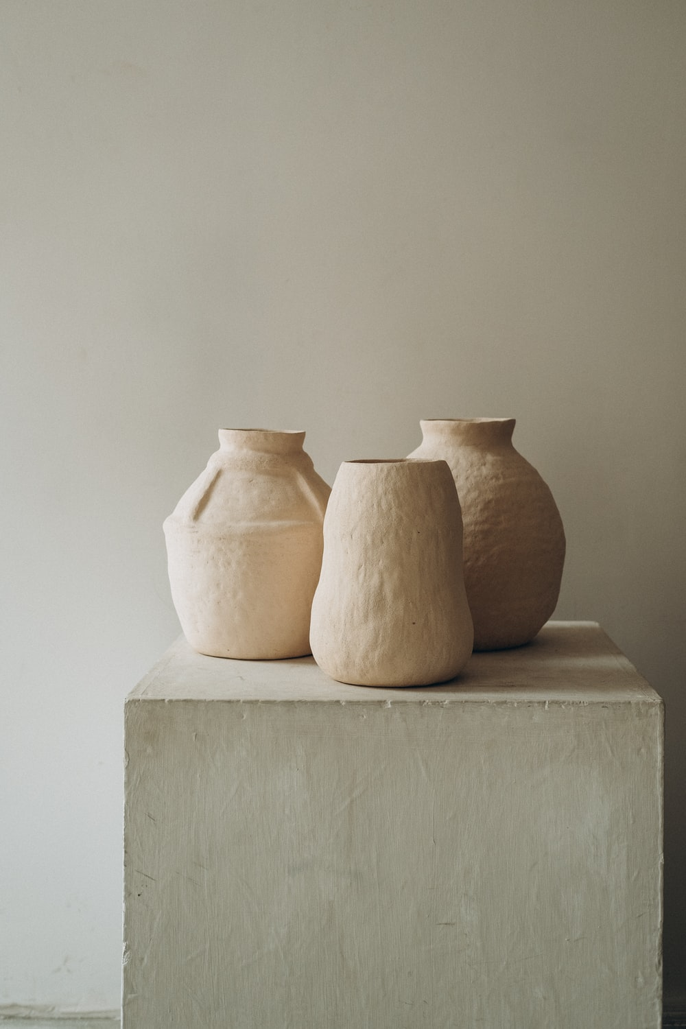 3 brown clay vases on white concrete table