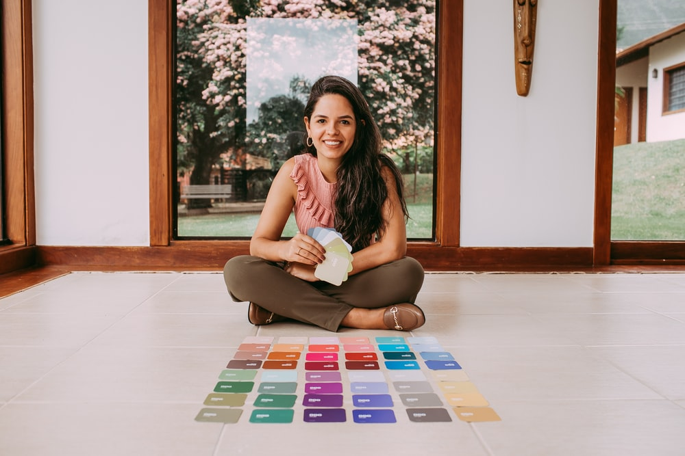 woman in white tank top sitting on white and blue puzzle mat