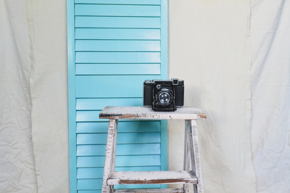 black and gray camera on blue wooden ladder