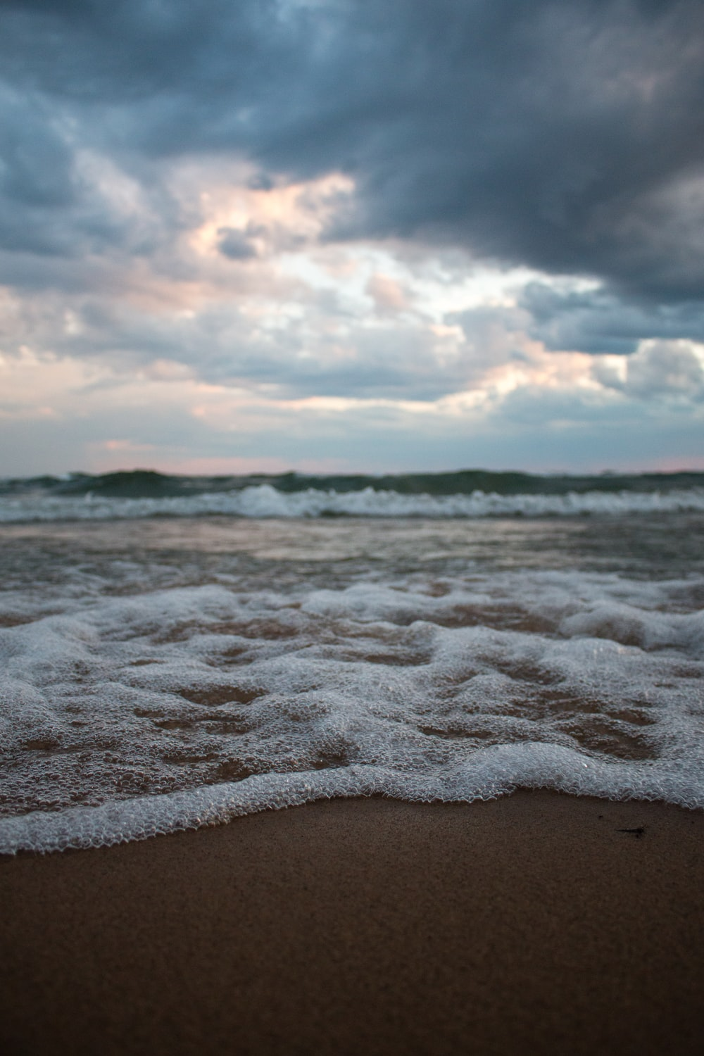 ocean waves crashing on shore under white clouds and blue sky during daytime