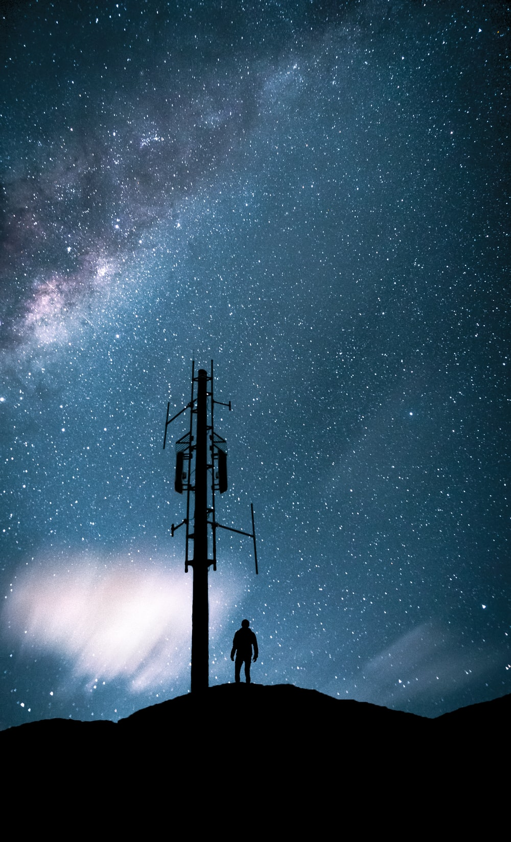 silhouette of people standing on top of electric post under starry night