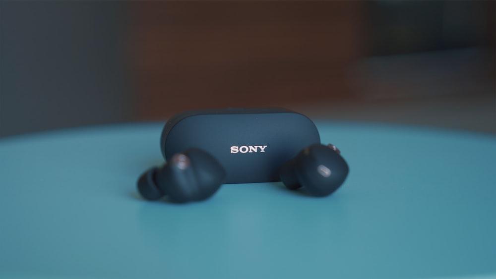 black sony headphones on blue table