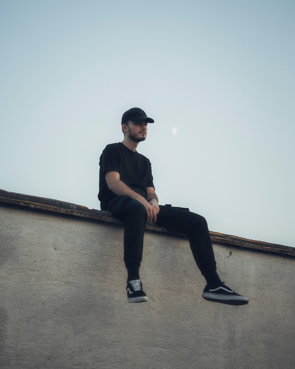 man in black shirt and black pants sitting on concrete wall