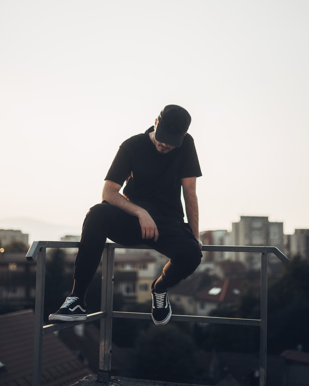 man in black crew neck t-shirt and black pants sitting on gray metal railings