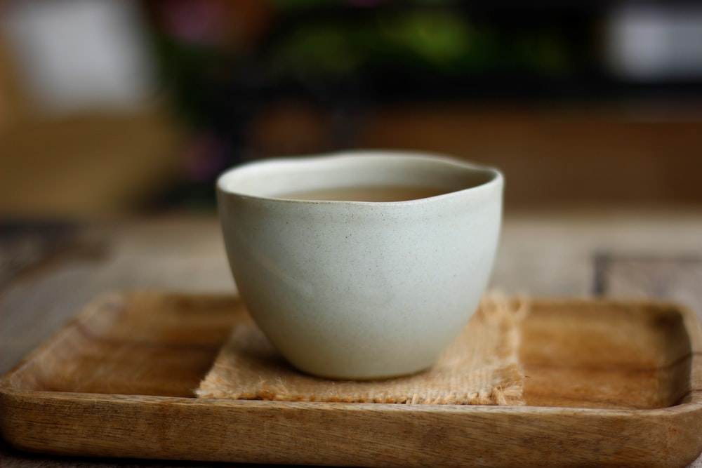 white ceramic cup on brown wooden table
