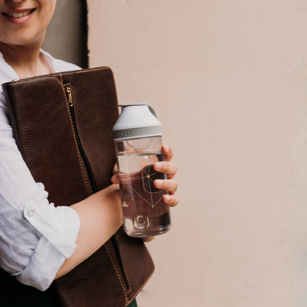woman in white shirt holding white and black plastic cup