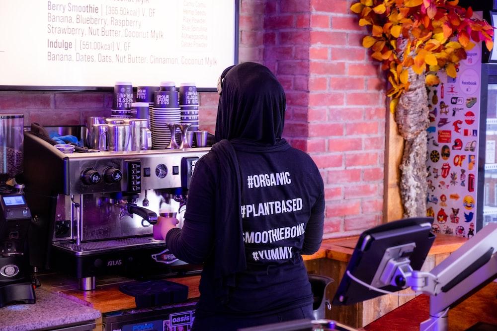 woman in black hoodie standing in front of black audio mixer