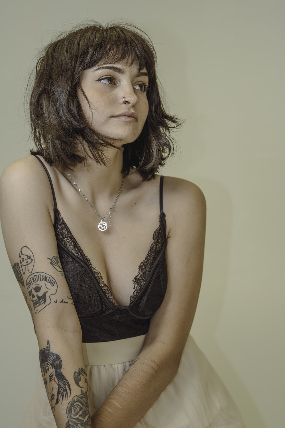 woman in black brassiere with tattoo on chest