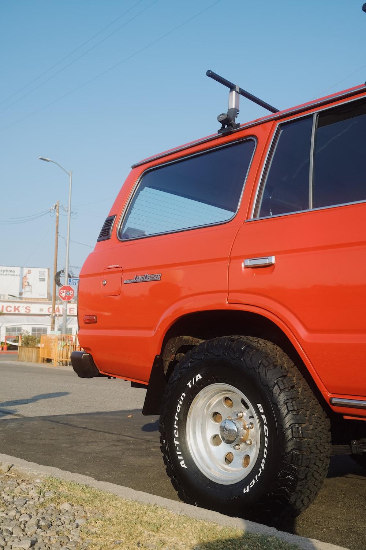 red suv on gray asphalt road during daytime