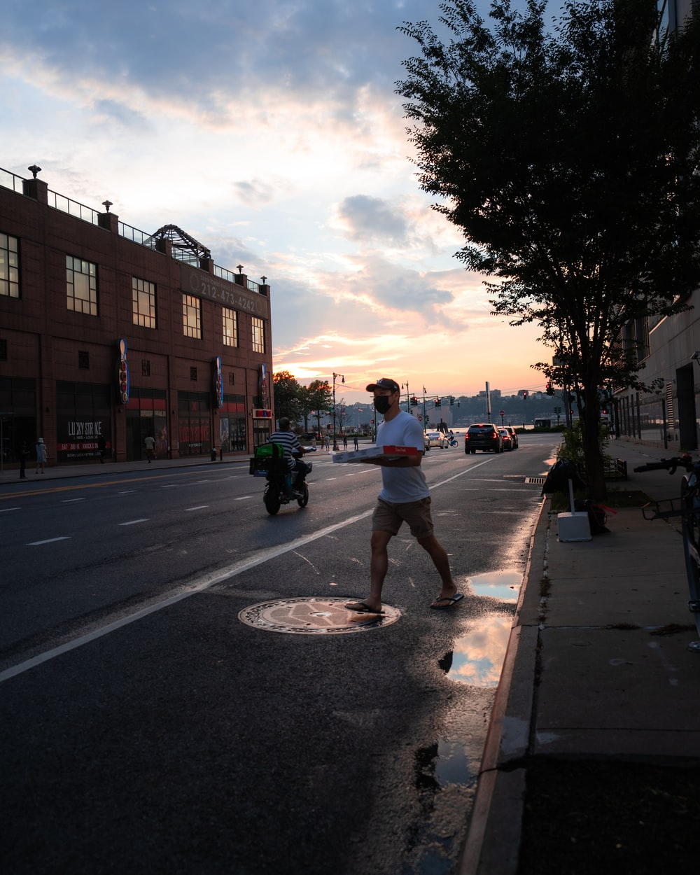 man in white t-shirt and blue denim jeans walking on sidewalk during daytime