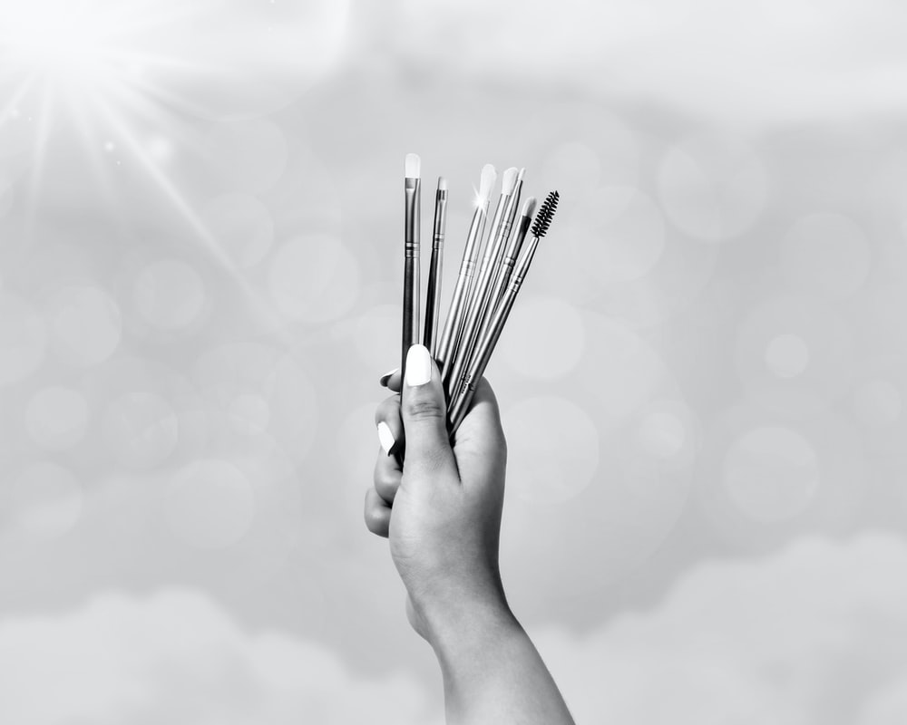 grayscale photo of person holding sticks