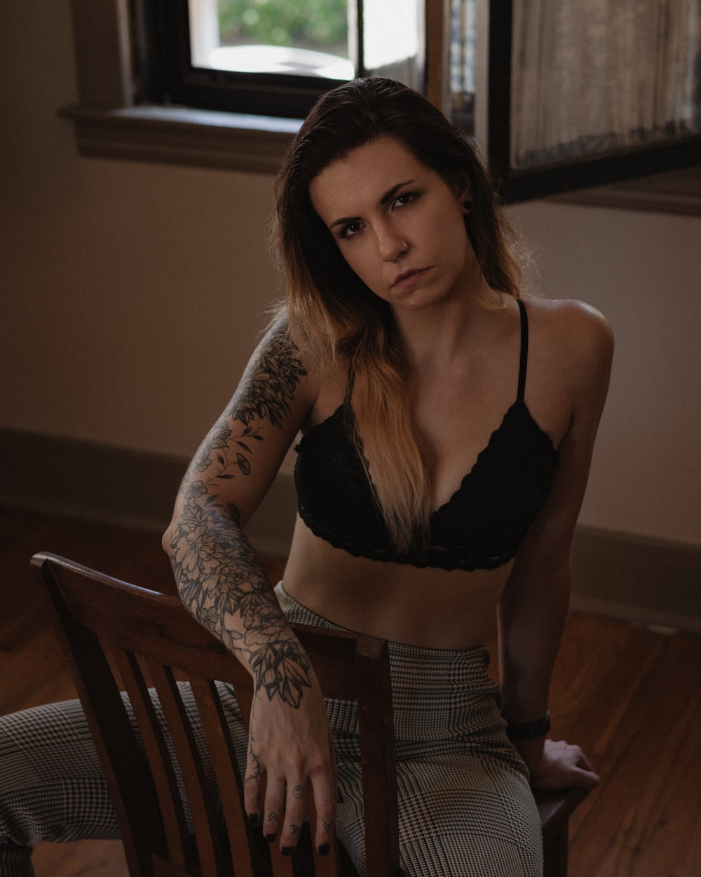 woman in black brassiere and gray pants sitting on brown wooden chair