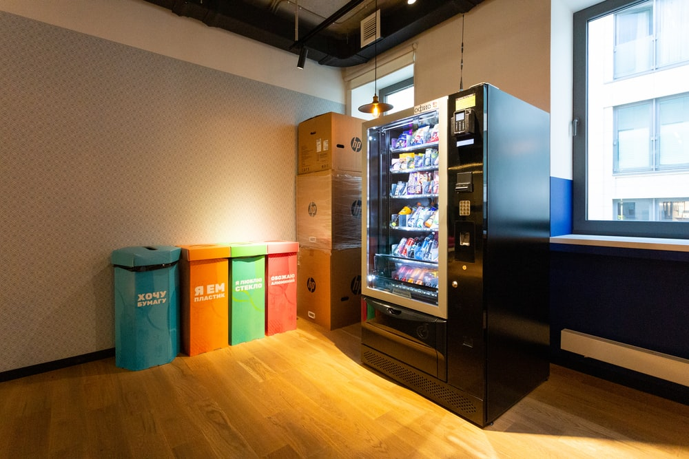 black and blue vending machine beside brown wooden cabinet