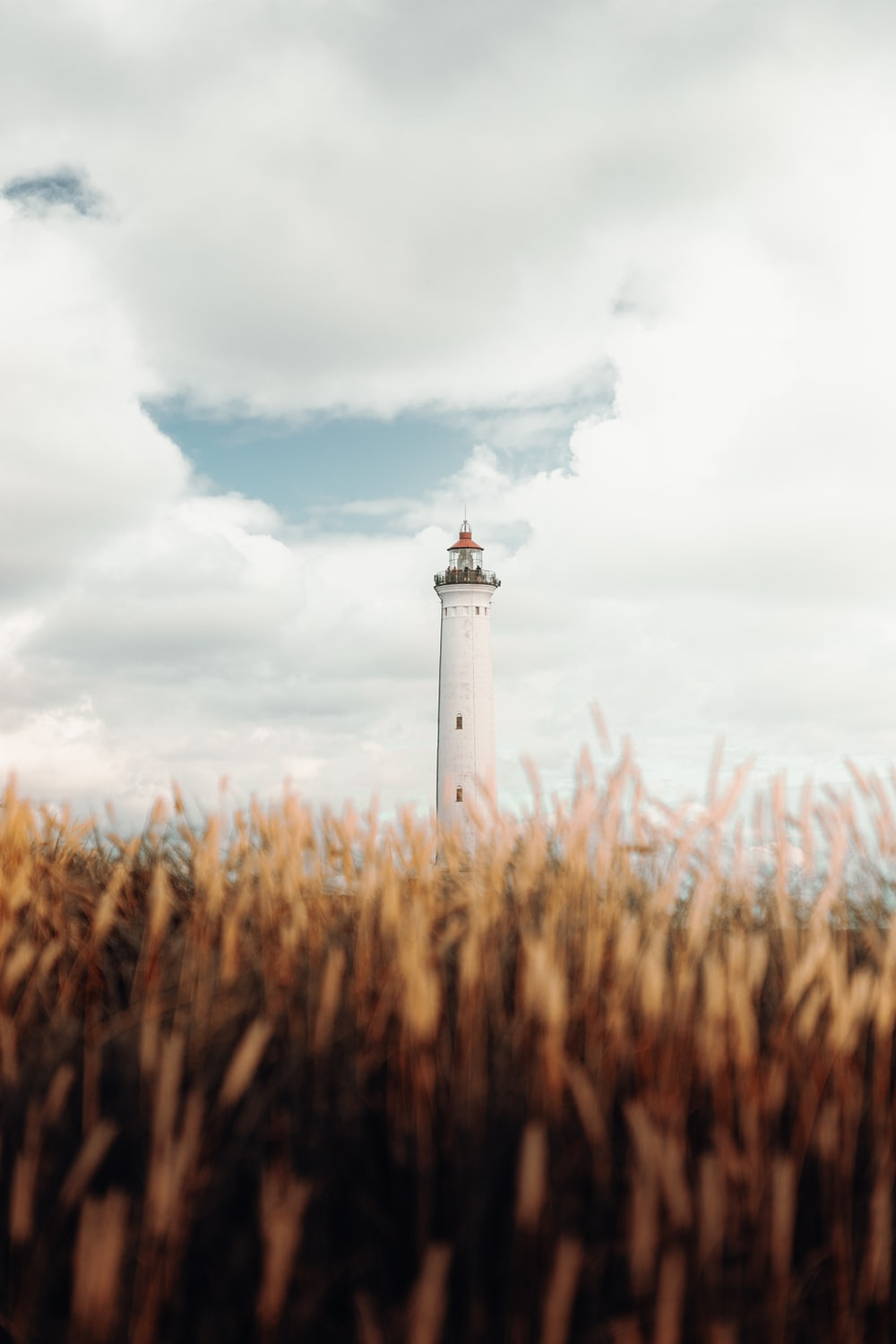white and brown lighthouse under cloudy sky during daytime