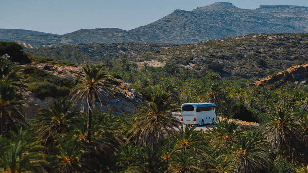 white van on green grass field near mountain during daytime