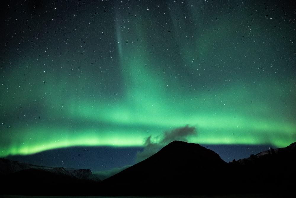 green aurora lights over black mountain