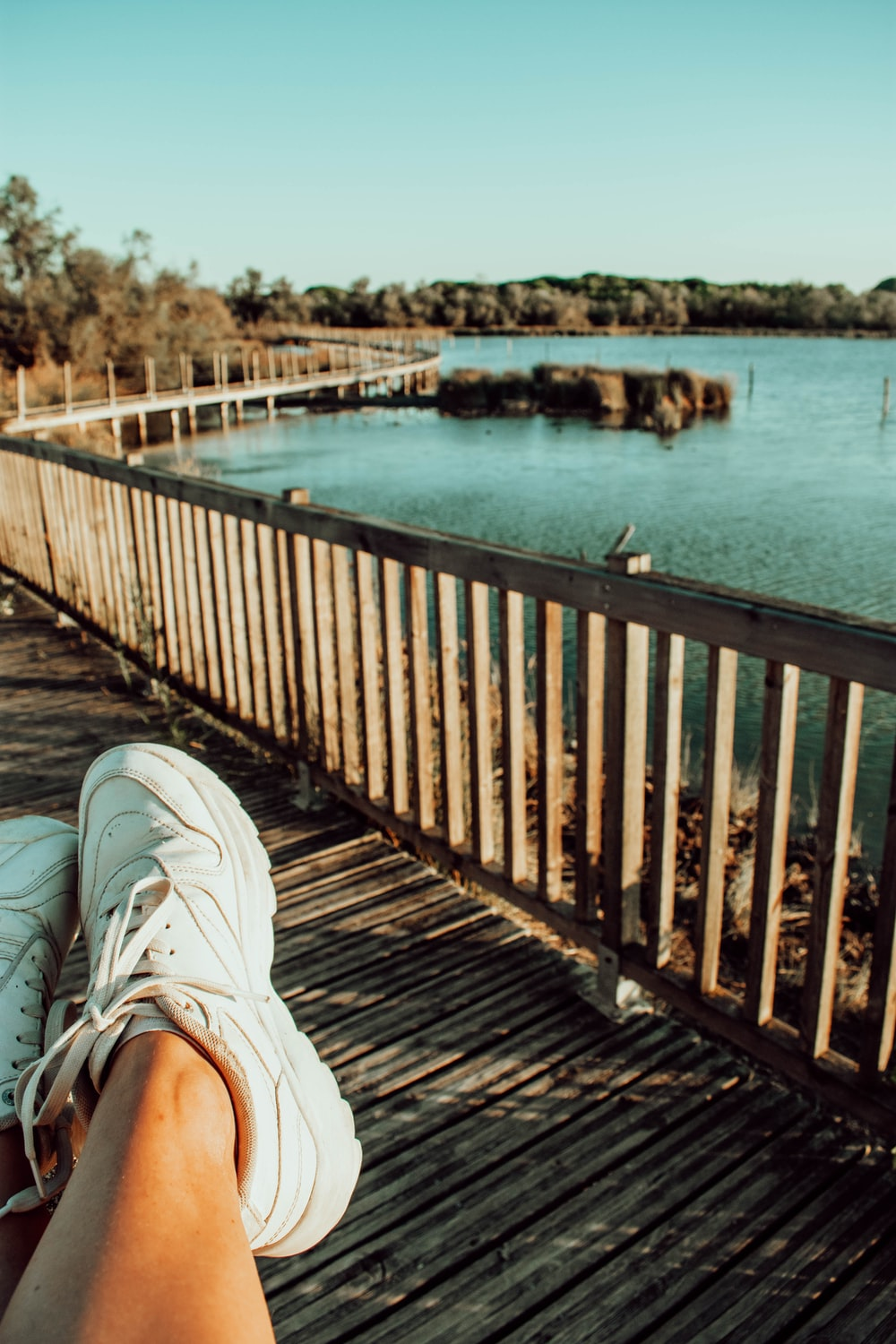 person in white sneakers sitting on wooden dock during daytime