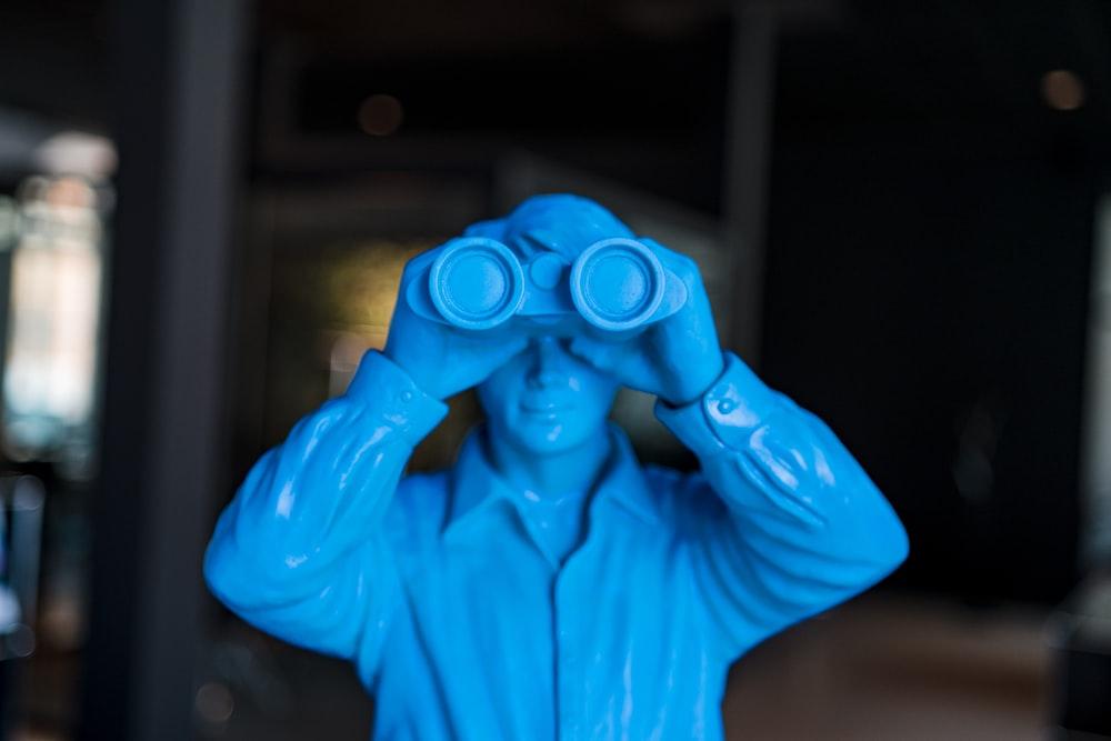 person in blue long sleeve shirt holding blue binoculars