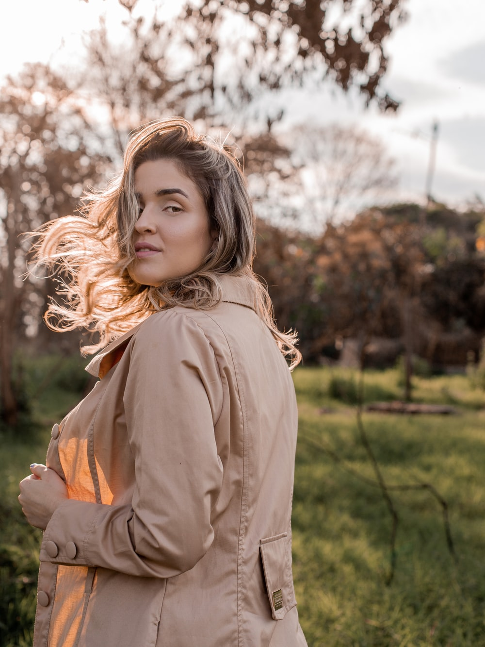 girl in brown coat standing on green grass field during daytime