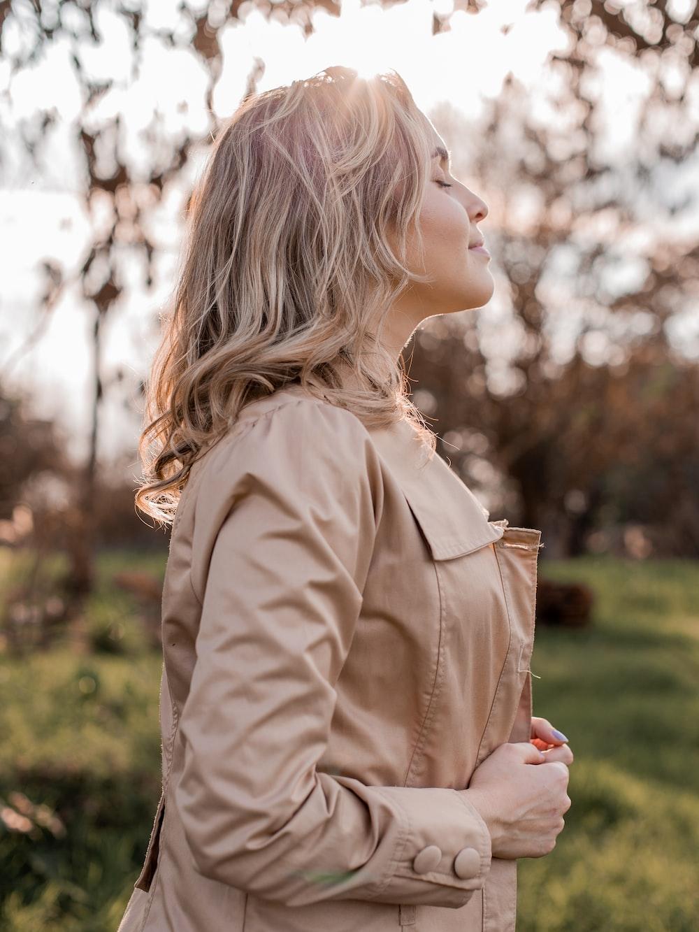 woman in brown coat looking down