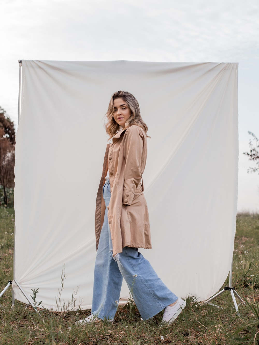 woman in brown coat and blue denim jeans standing on white textile