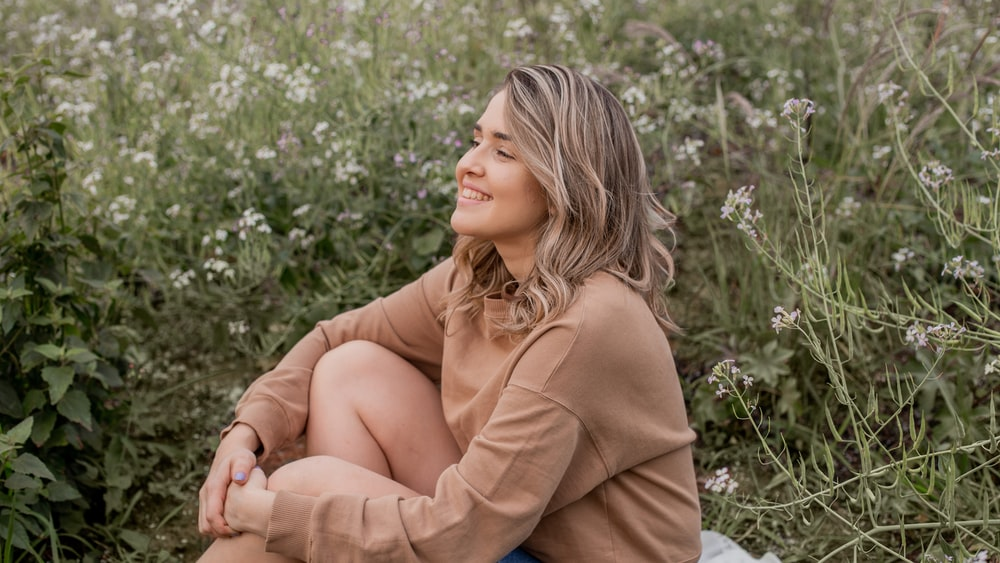woman in brown long sleeve shirt sitting on green grass during daytime
