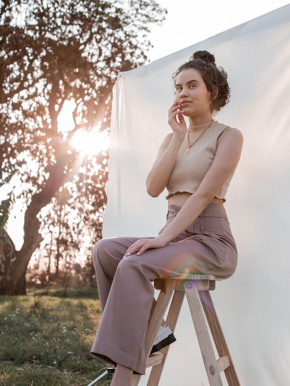 woman in white tank top sitting on brown wooden folding chair during daytime