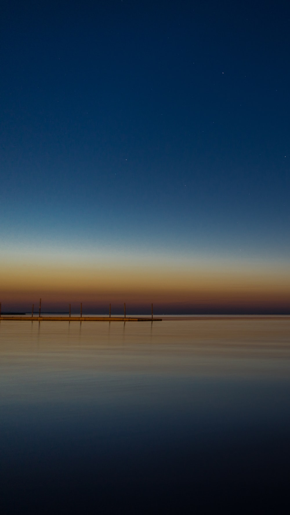 calm sea under blue sky during sunset