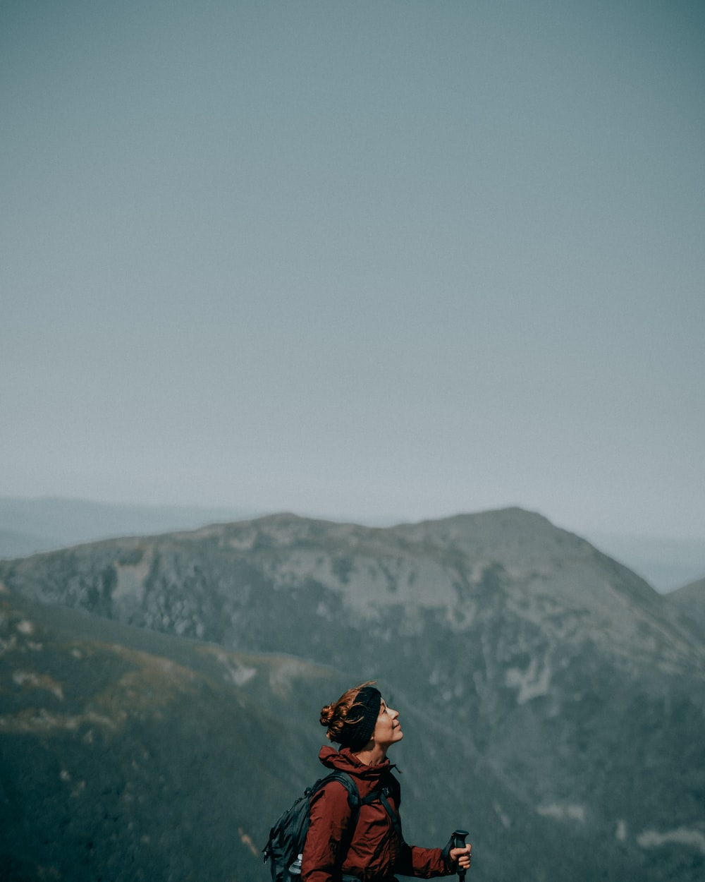 man in black jacket and black backpack standing on mountain during daytime