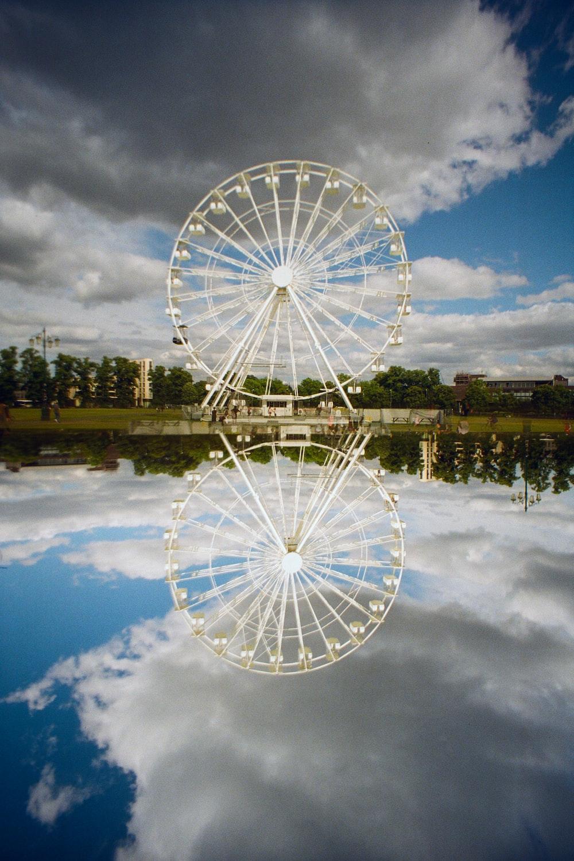 white ferris wheel near body of water during daytime