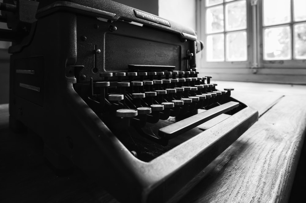 black and gray typewriter on table