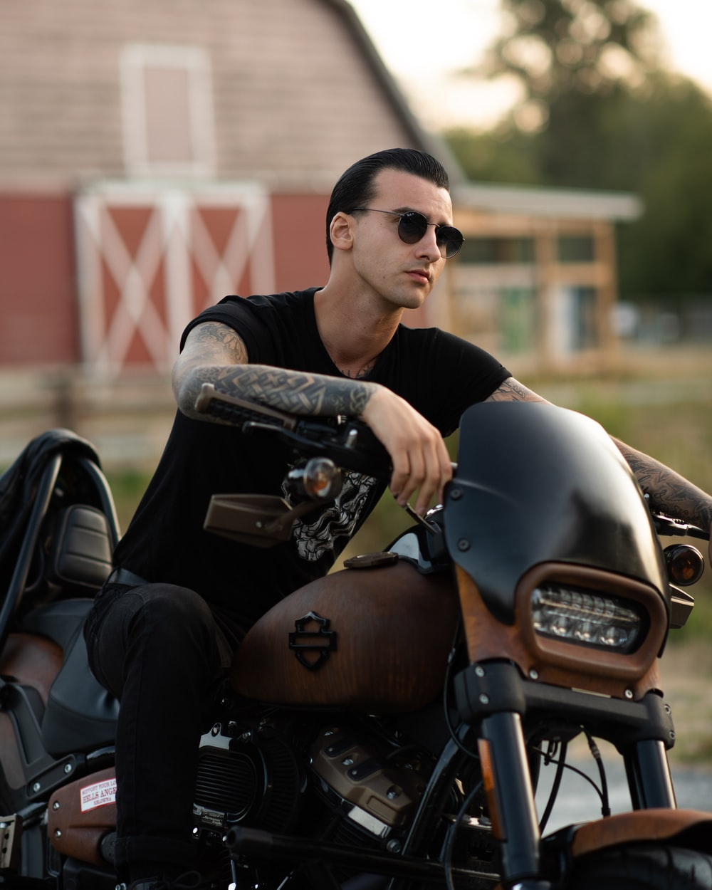 man in black crew neck t-shirt and black sunglasses sitting on black motorcycle