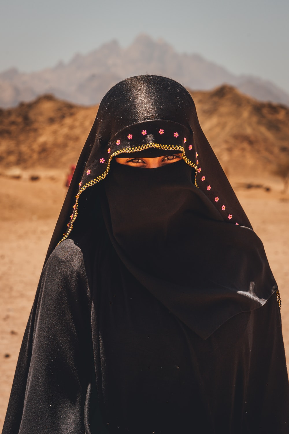 person in black hijab standing on brown field during daytime
