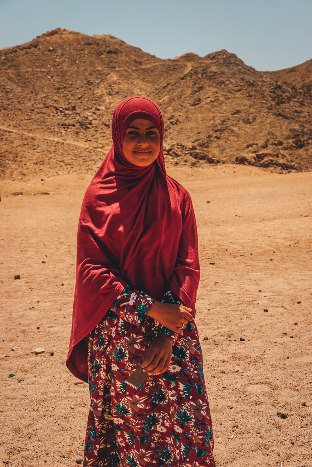 woman in red hijab standing on brown sand during daytime