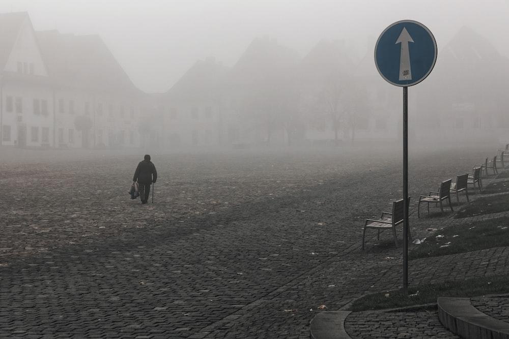 man in black jacket walking on sidewalk during foggy day