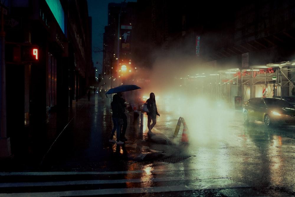 man and woman holding umbrella walking on sidewalk during night time