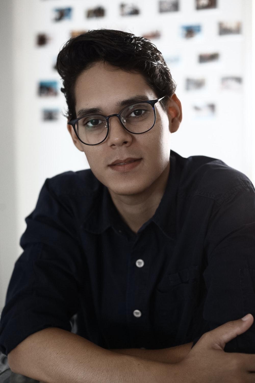 man in black dress shirt wearing black framed eyeglasses