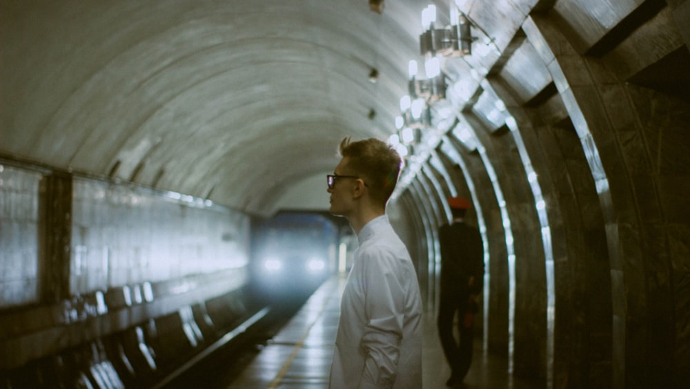 man in white dress shirt standing on train station