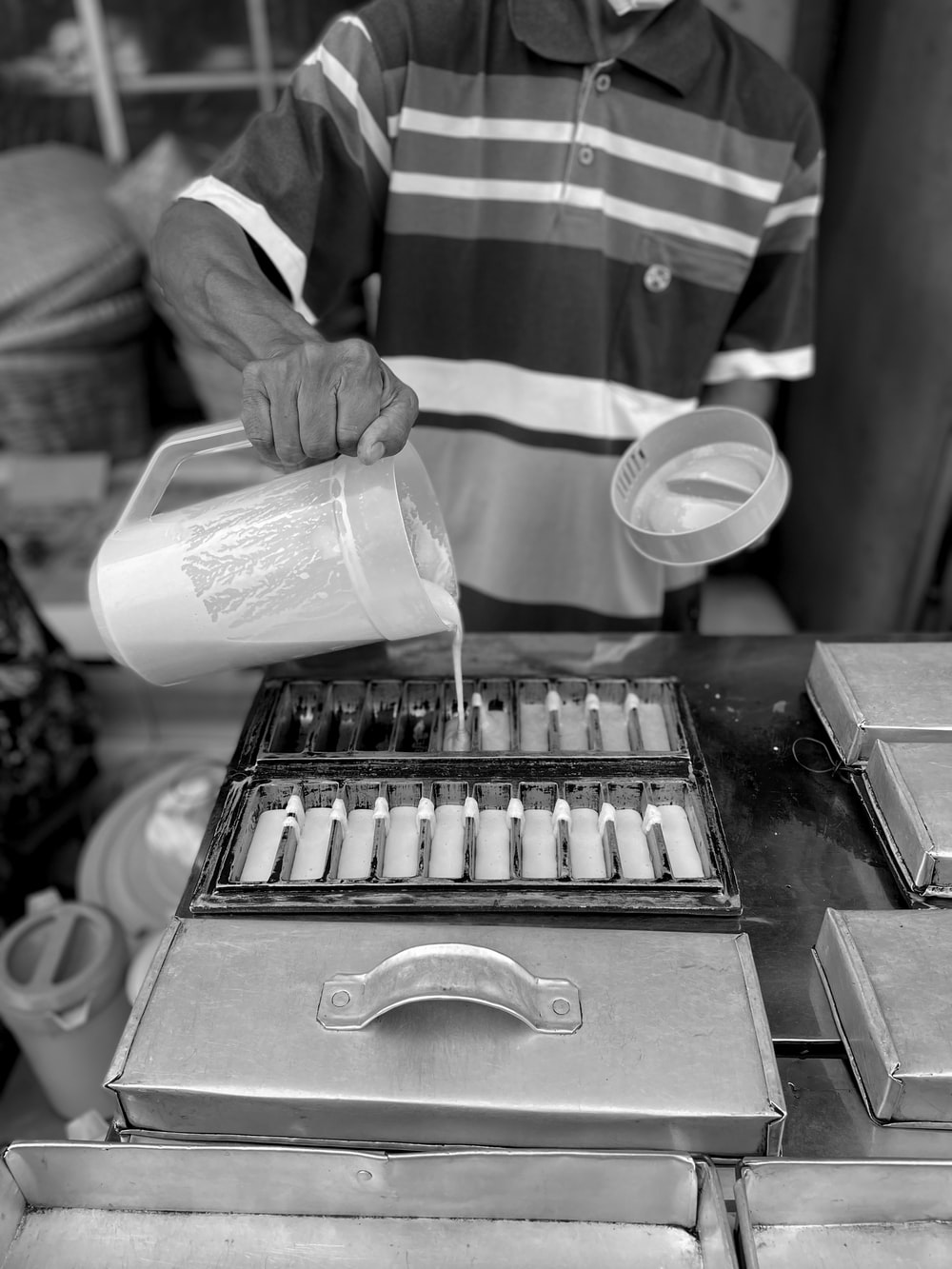 grayscale photo of person pouring water on cup