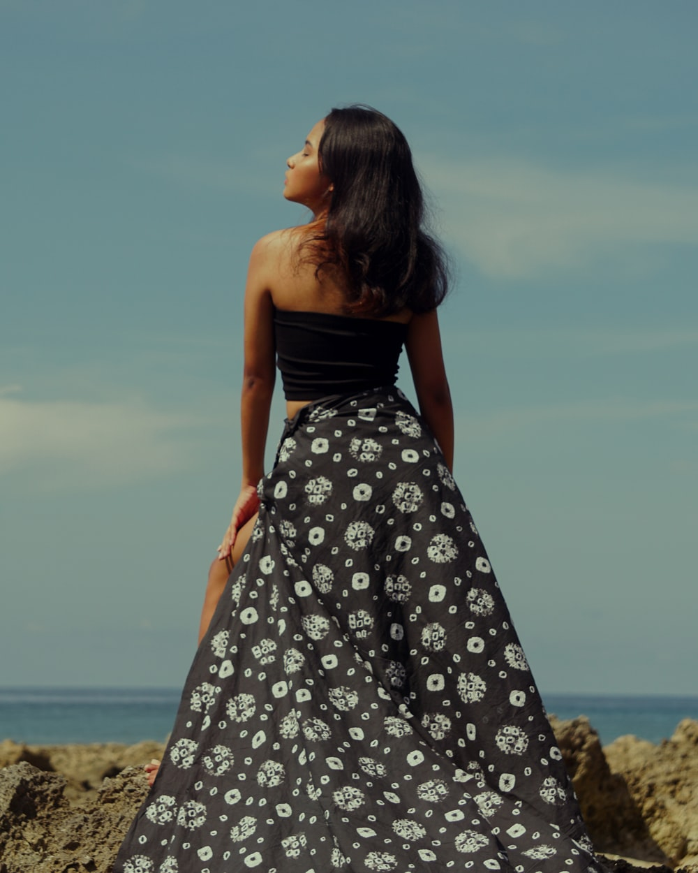 woman in black and white floral tube dress standing on brown sand during daytime