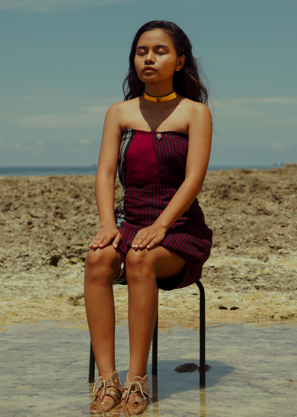 woman in black and red sleeveless dress sitting on chair on beach during daytime