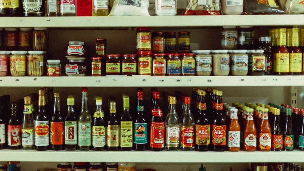 assorted bottles on brown wooden shelf