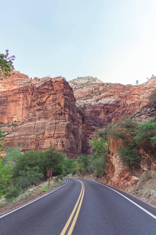 gray asphalt road between brown rock formation during daytime