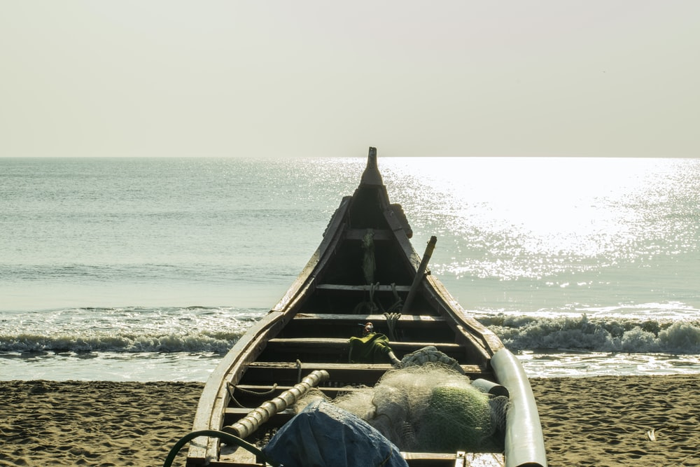 brown wooden boat on beach during daytime